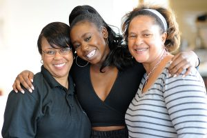 AFCA co-chair Tracey Stanley, at left, and AFCA member Rosalind Adgers, at right, congratulate Sadasia McCutchen '17 on her upcoming graduation.