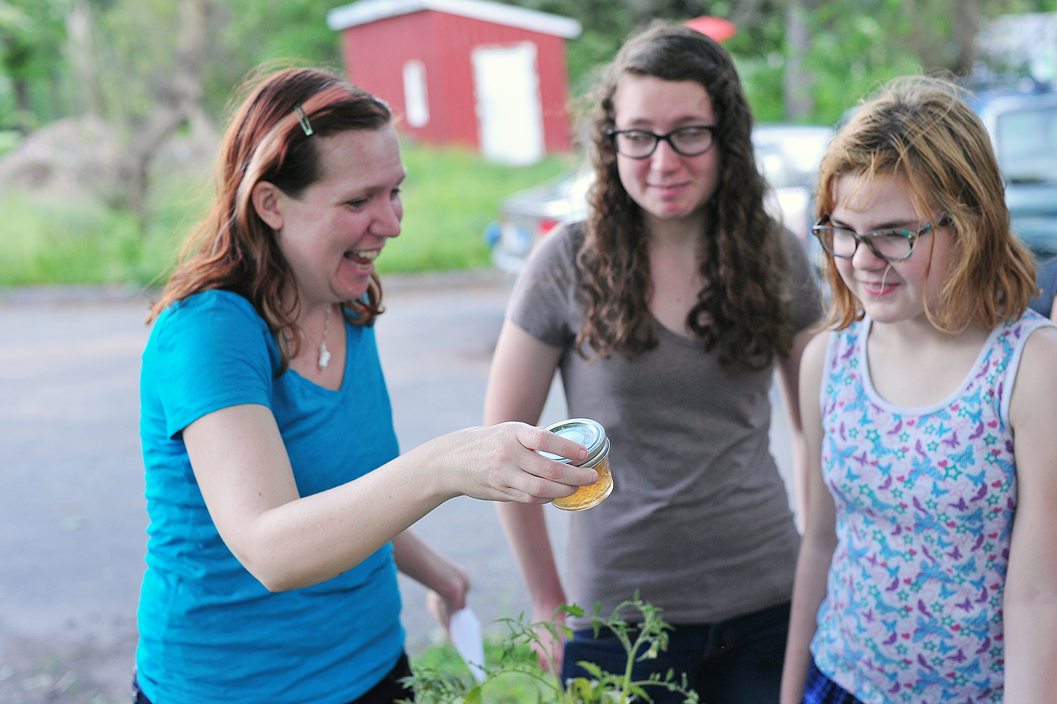 "Anika Dane, administrative assistant for the Molecular Biology and Biochemistry Department, shops for dandelion jelly with her daughters, Kerste and Aeris. ""Aeris confirms the jelly tastes like honey,"" Dane said."