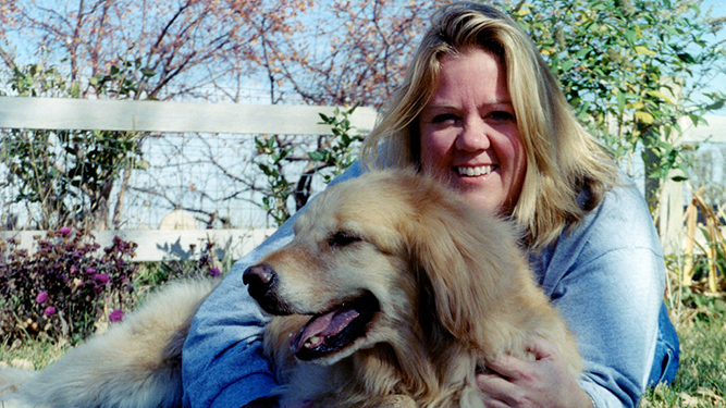 Laura Fraser's sister Jan, smiling, with her arms around her dog, Sunny.