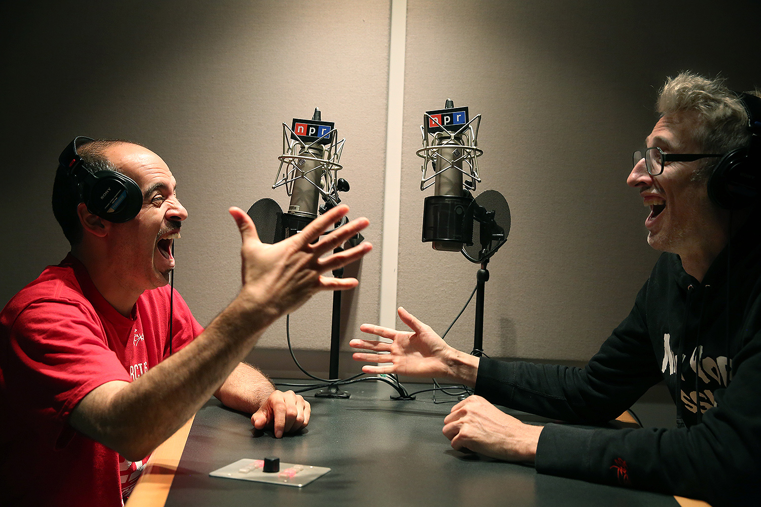Bobbito Garcia and DJ Stretch Armstrong are in animated discussion and laughter across a studio table on the air at NPR.