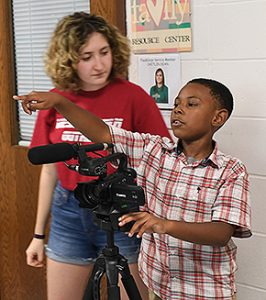 Sarah Lucente '21 works with MacDonough students Isaiah and Violet on how to operate the videocamera.