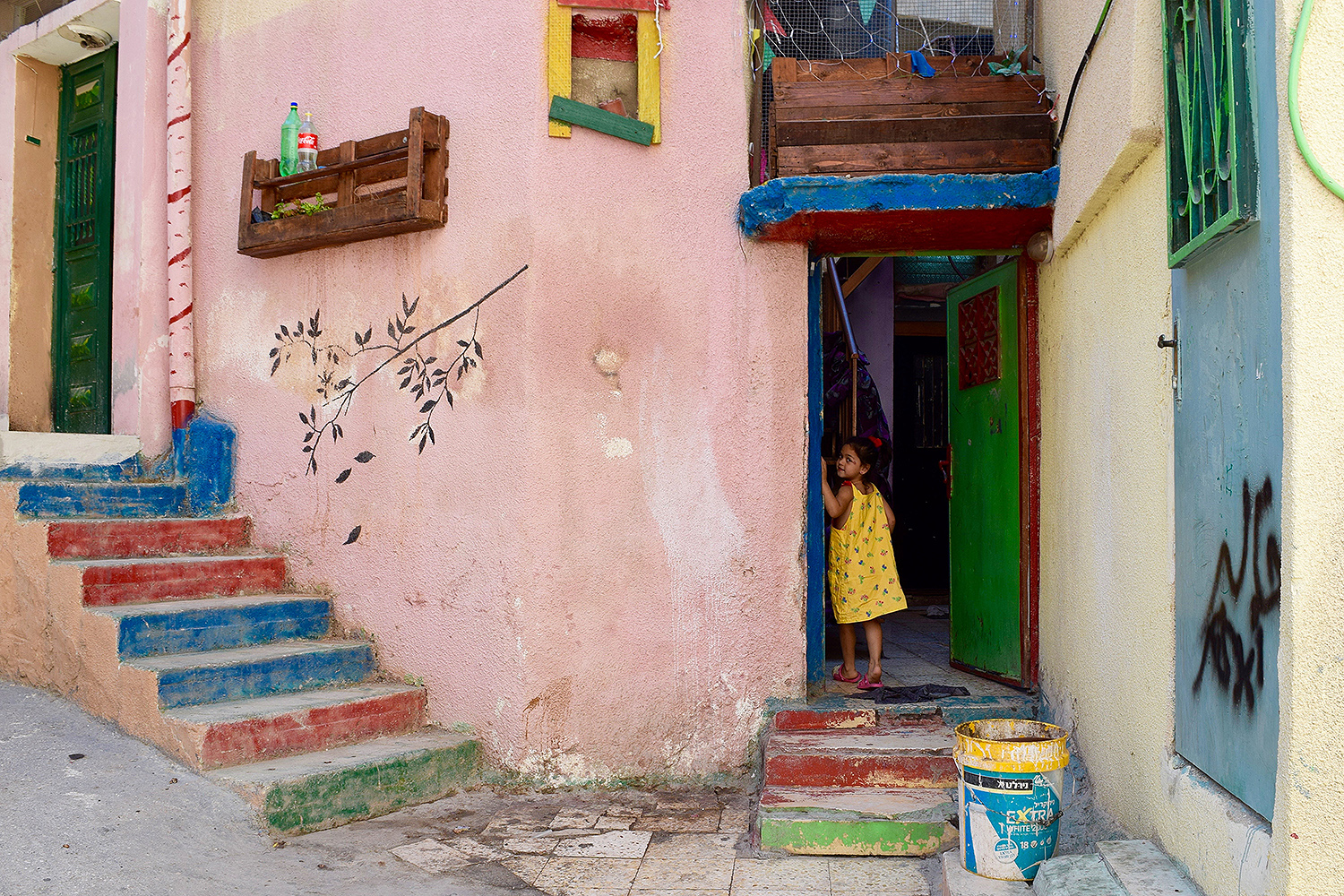 "Aida"" by Isabel Steckel, '19; Bethlehem, Palestine ""A little girl in yellow looks back and smiles at me before entering her family's house at the Aida Refugee Camp -- home to more than 5,500 Palestinian refugees -- in the central West Bank."""