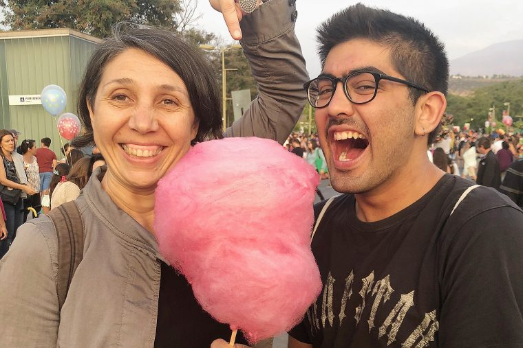 "Marcela Oteíza, assistant professor theater, and Ryan Dobrin '18 snack on cotton candy prior to the ""Beringei"" production at the Festival Internacional Santiago a Mil in Santiago, Chile. Inspired by the name of one of the most threatened species of gorilla in the world, Beringei is a street show of large mechanical puppets that raise awareness of the gorillas' risk of extinction."