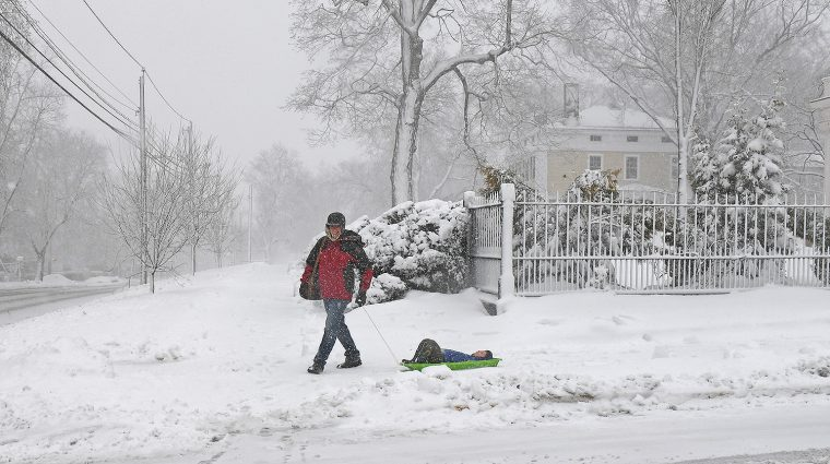 Emmanuel Paris-Bouvet, director of language resources and technology and visiting instructor in romance languages and literatures, pulls his son, Lucas, down Wyllys Ave. in a sled. (Photo by Olivia Drake)