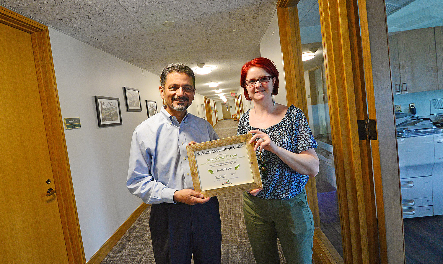 Antonio Farias, vice president for equity and inclusion, and Megan Flagg, executive assistant to the provost and vice president for academic affairs, proudly display their Green Office Certification on the third floor of North College. The third floor is the first space on campus to be Green Office Certified by the Sustainability Office.