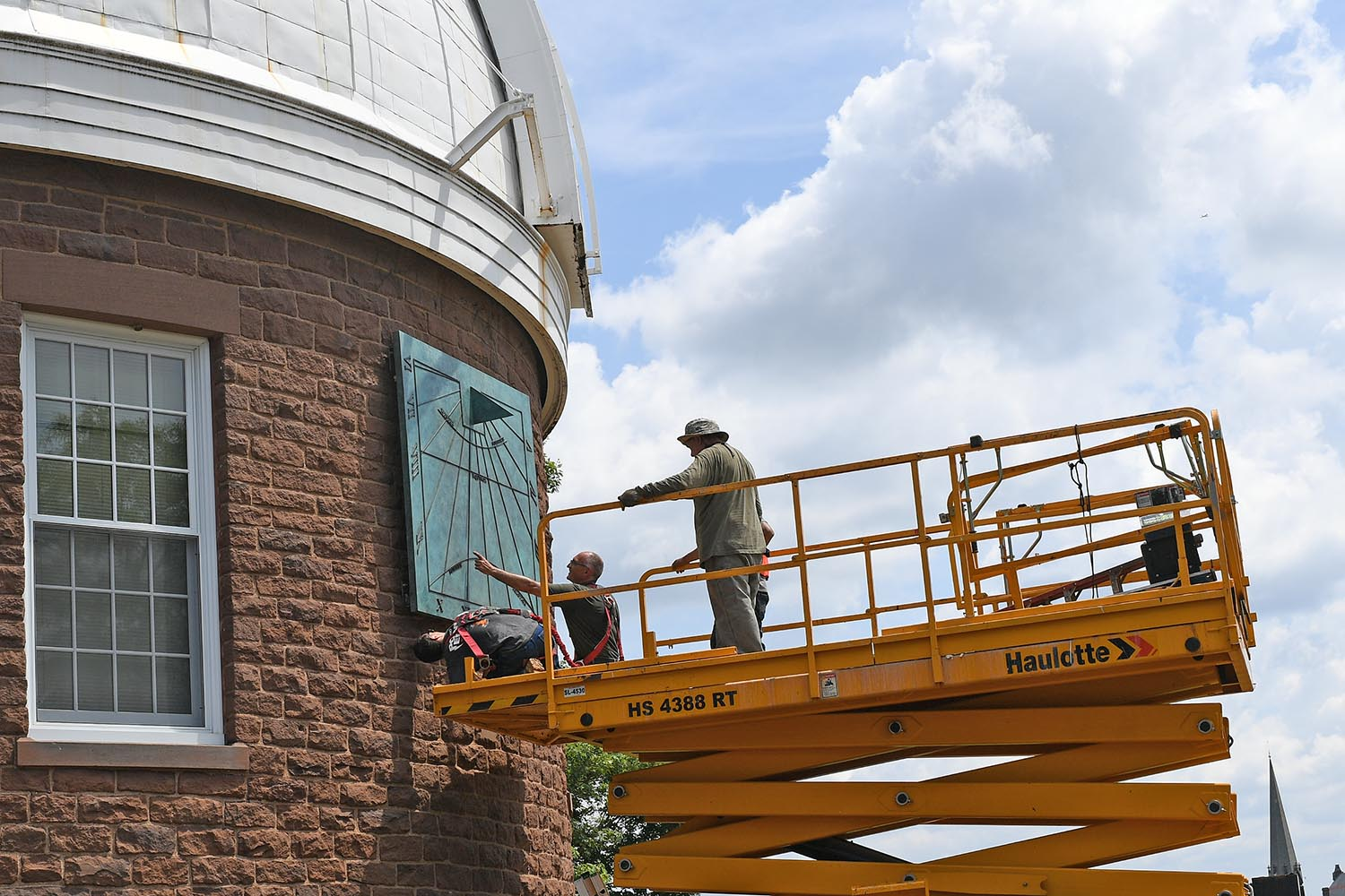 "Adzema chose to color the bronze sculpture in a patina. ""I chose this green because it is the natural color bronze would oxidize over time. It is also a green that looks great against the color of the Observatory's brownstone walls,"""
