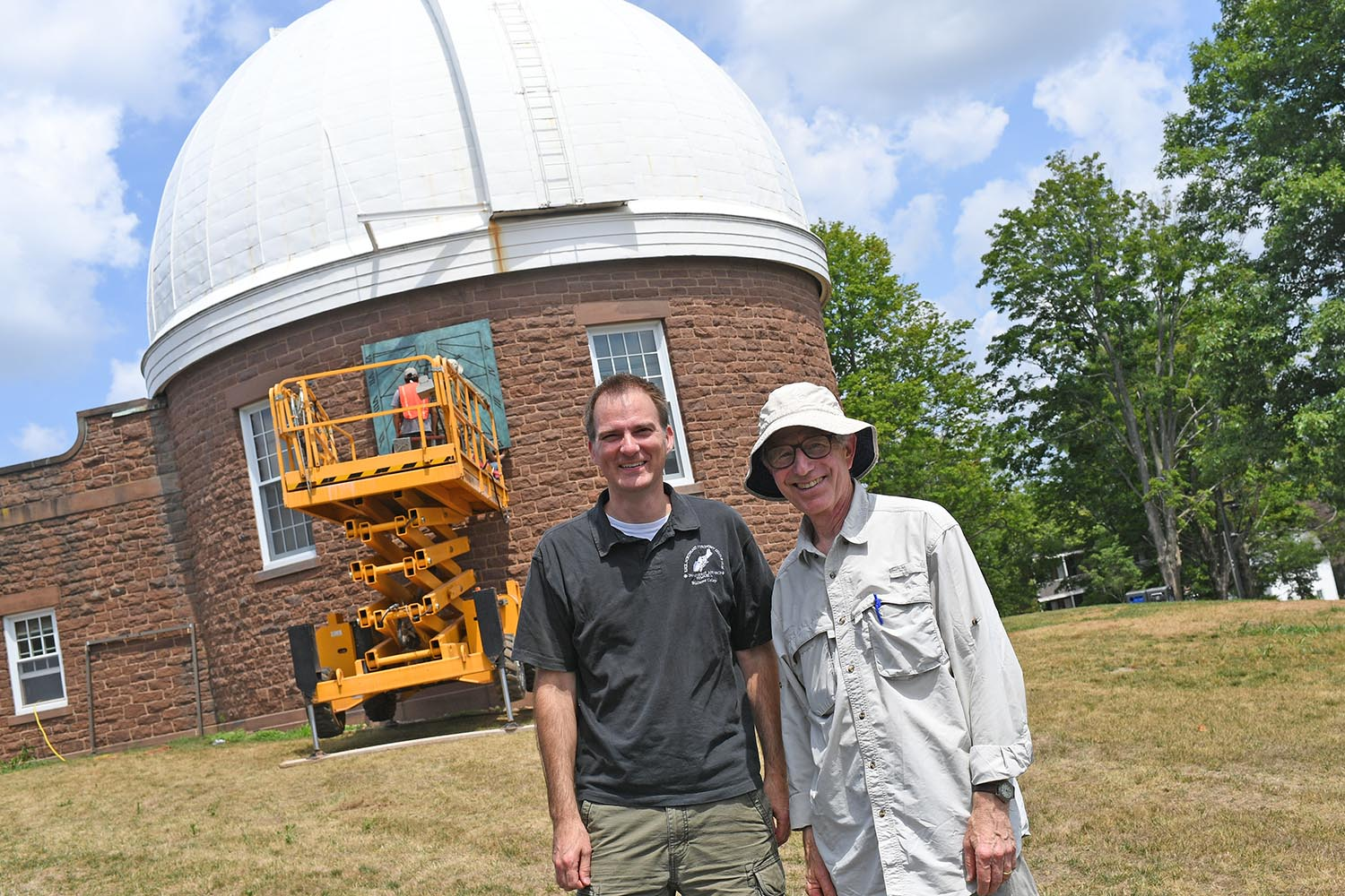 Seth Redfield, chair and associate professor of astronomy, associate professor of integrative sciences, and artist Robert Adzema observe a sundial's installation July 16 at the Van Vleck Observatory. Adzema, a maker of site-specific sundials, designed the sculpture to be placed at its exact location on the telescope's wall.