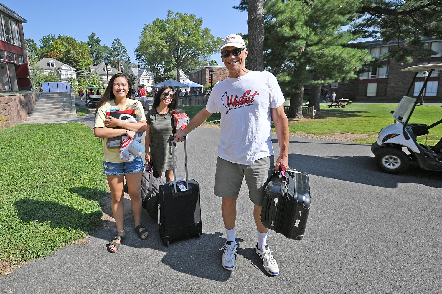 Wesleyan President Michael Roth '78 helps a student move into her residence in the Butterfields.