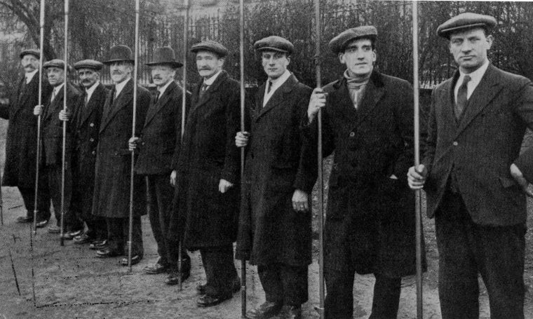 A team of British lamplighters pose with their poles c. 1930. (Chris Sugg, CC BY-SA)