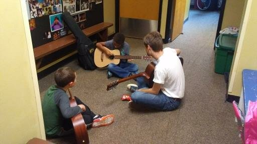 Musical Mentor Henry Hodder '20 works with two of his guitar students at Oddfellows Playhouse in Middletown.