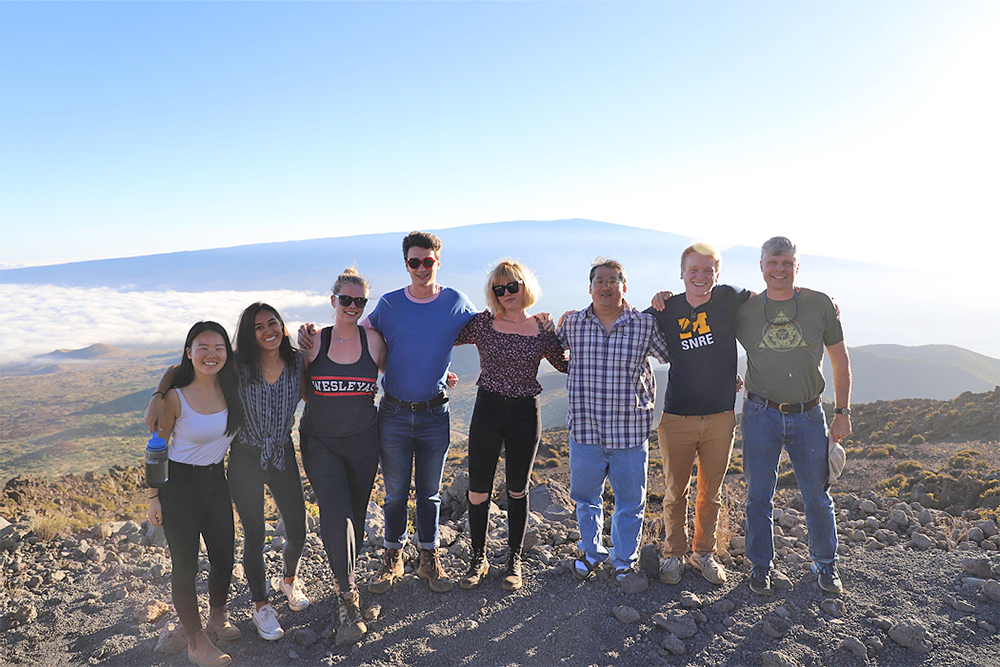 Left to right: Kelly Lam, Sara Wallace-Lee, Jacqueline Buskop, John Sheffer, Celeste Smith, Tim Ku, Ryan Nelson, and Phil Resor. Photo taken at in January 2019 atop Mauna Kea at >10,000 feet above mean sea level with Mauna Loa in the background.