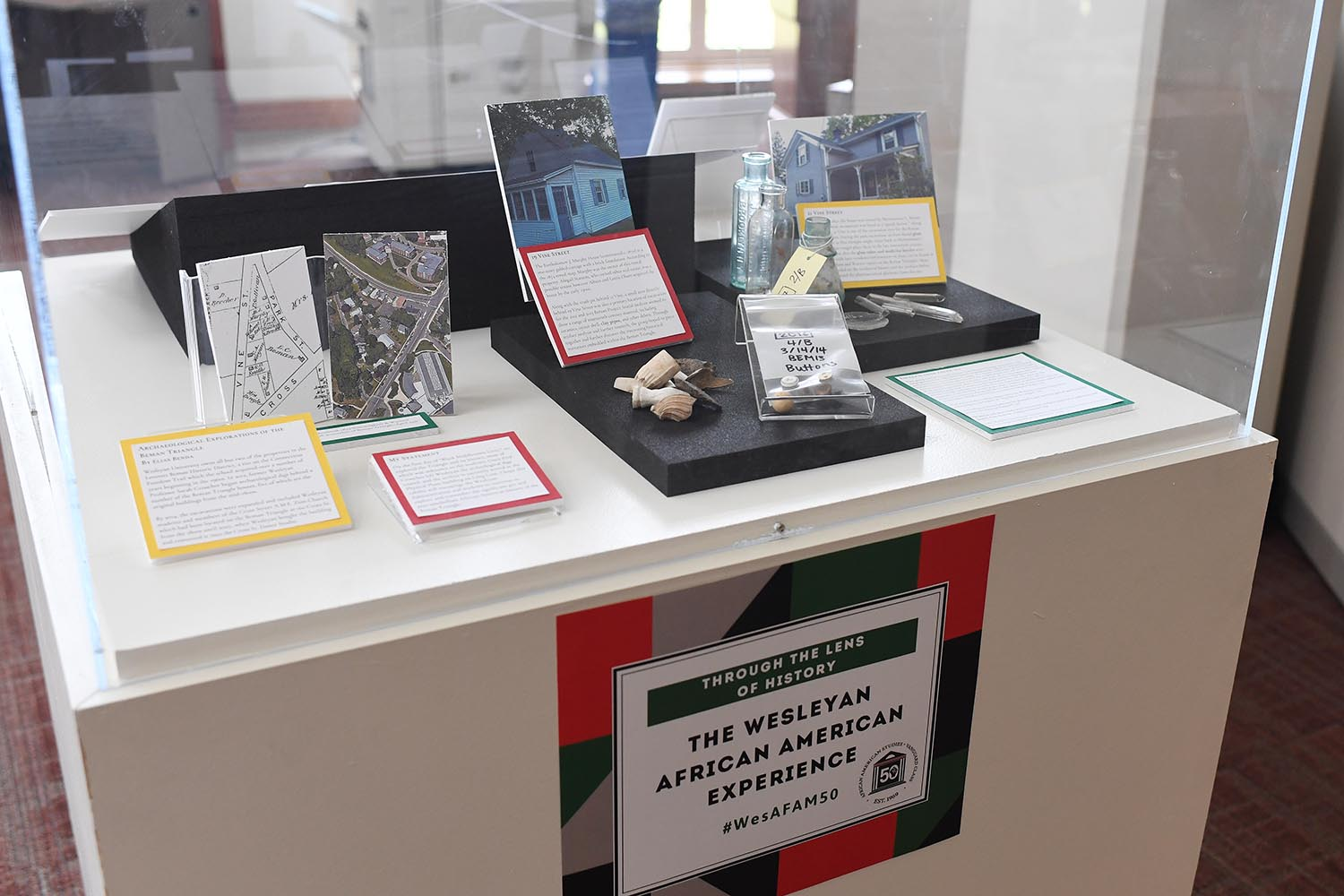 "Student-curated mini-exhibits are displayed inside cubed-cases in the Olin Reading Room. Pictured is a display titled ""Unburying Black Middletown History: Archaeological Findings From the Beman Triangle."" curated by Arianne Philemy '21."