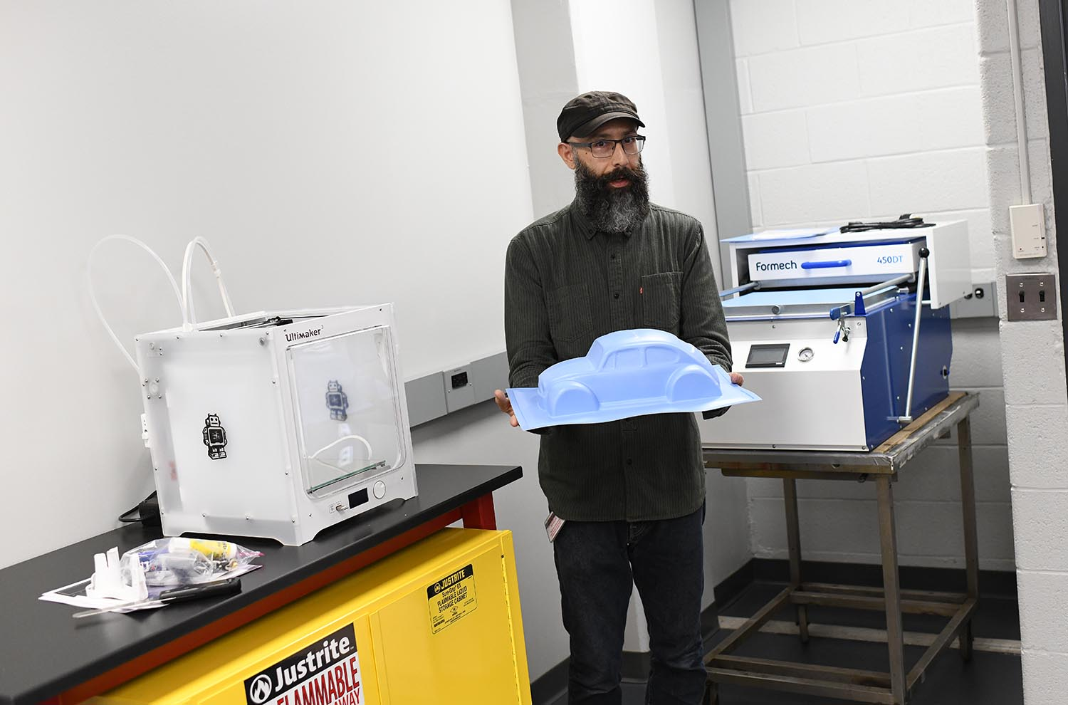Lopez shows off a vacuum forming tool, which is used to form plastic around a mold and create a permanent object. At left is a 3-D printer.