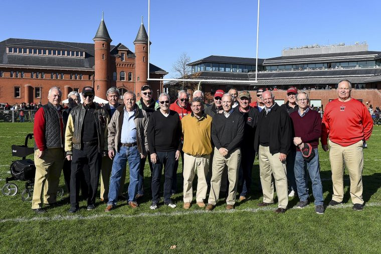 1960s Alumni Athletes and Athletic Director stand on the field