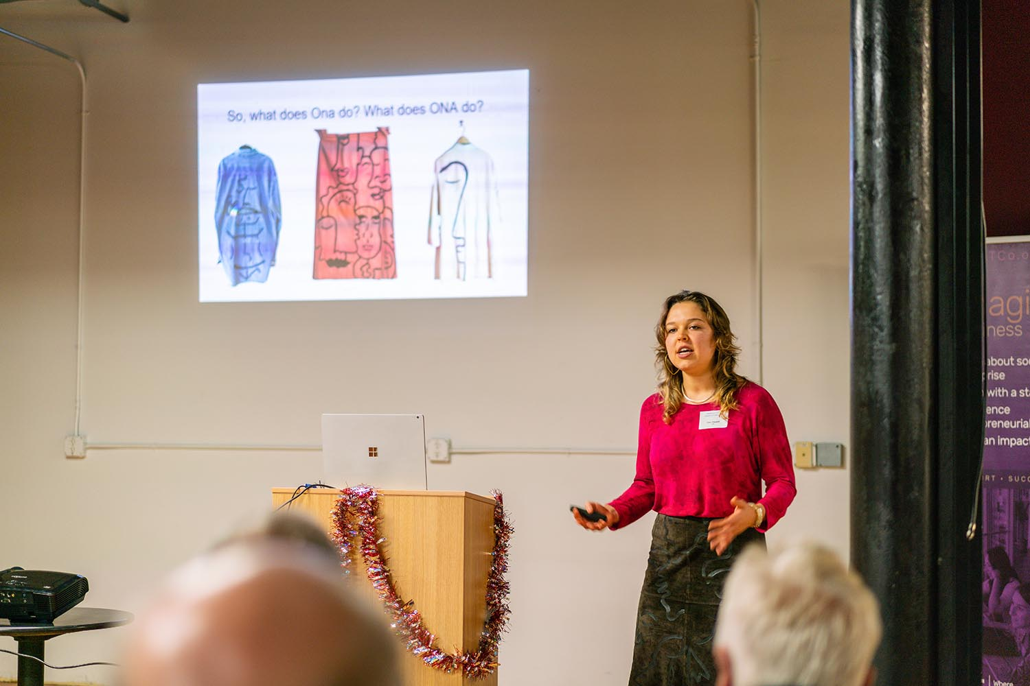Ona, in front of a slide illustrating clothing, discusses the clothes she designs