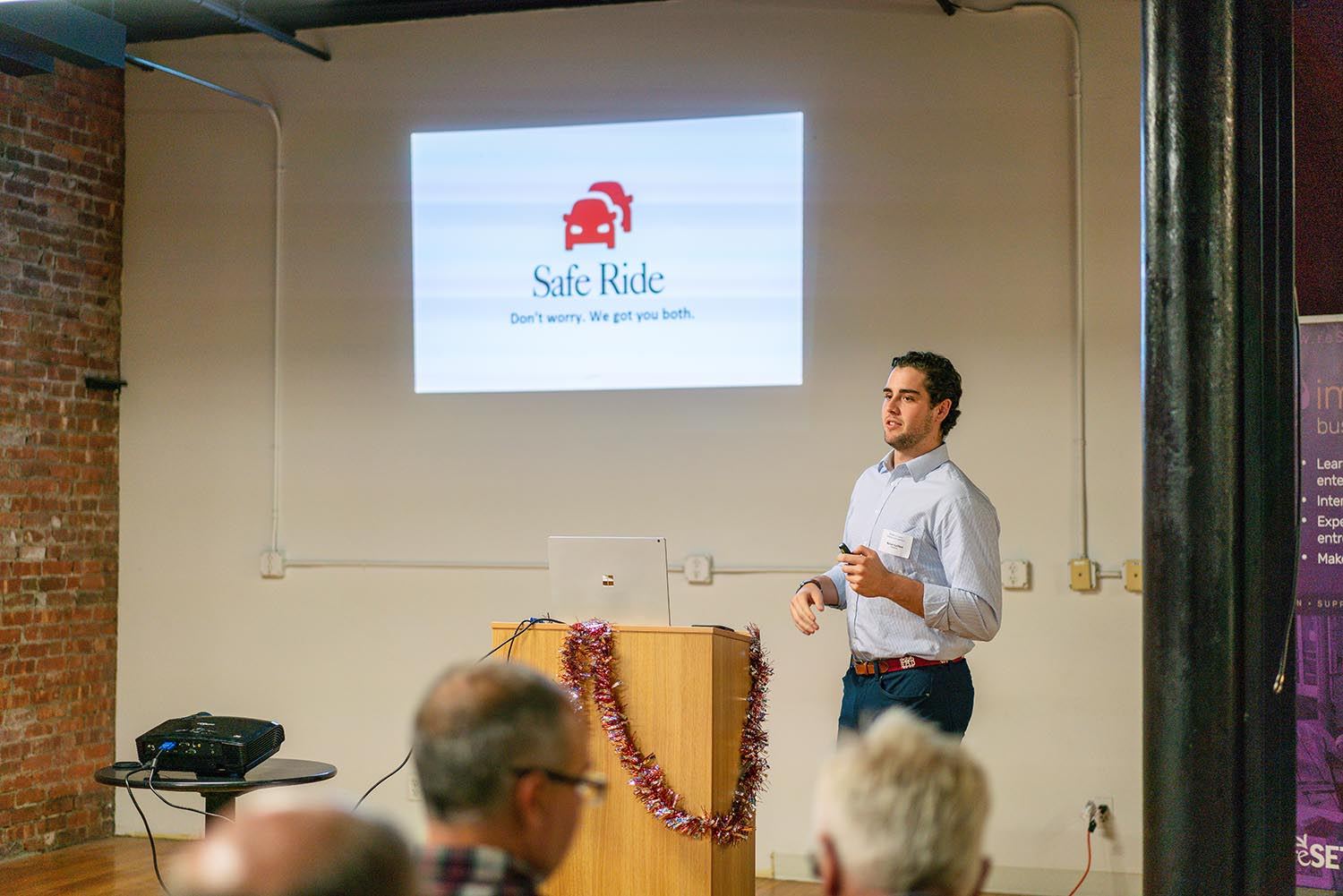 Nolan stands in front of the screen with his logo for Safe Ride