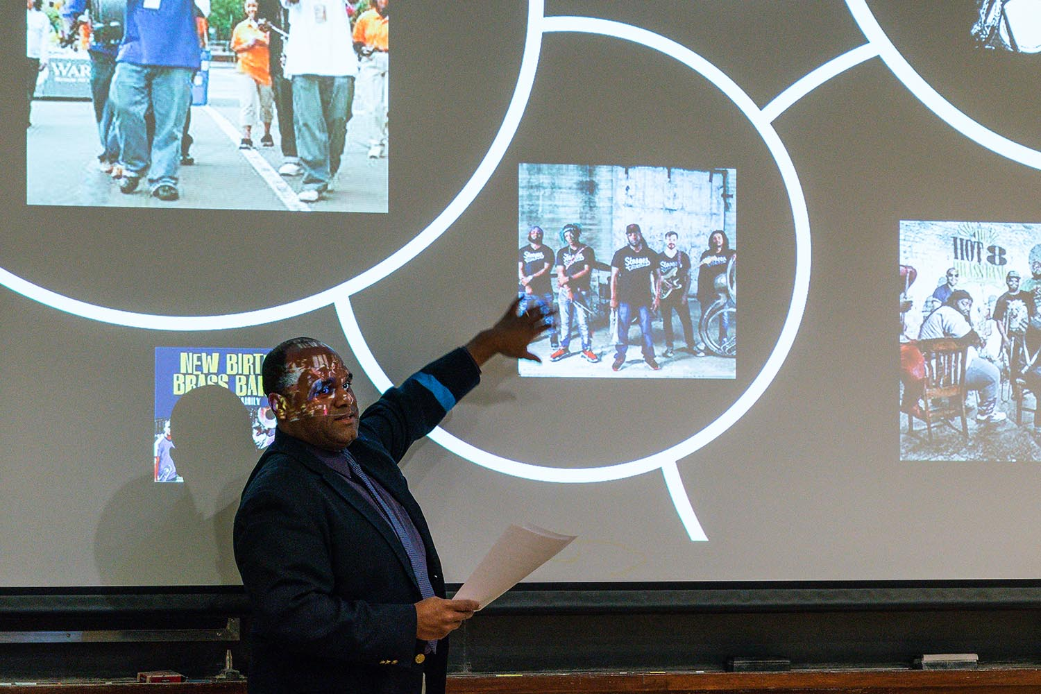 "McNeil explained how the institution of the Black New Orleans brass band represents a genealogic continuum that extends back to the arrival of the first enslaved Africans to the Louisiana Territory. ""This continuum connects a violent past, marked by physical abuse of black bodies in the form of institutionalized slavery, to a violent present confounded by systemic poverty, social injustice, and police brutality,"" he said. In spite of extreme oppression, the brass band community continues to enrich and enliven both local communities through their iconic musical offerings."
