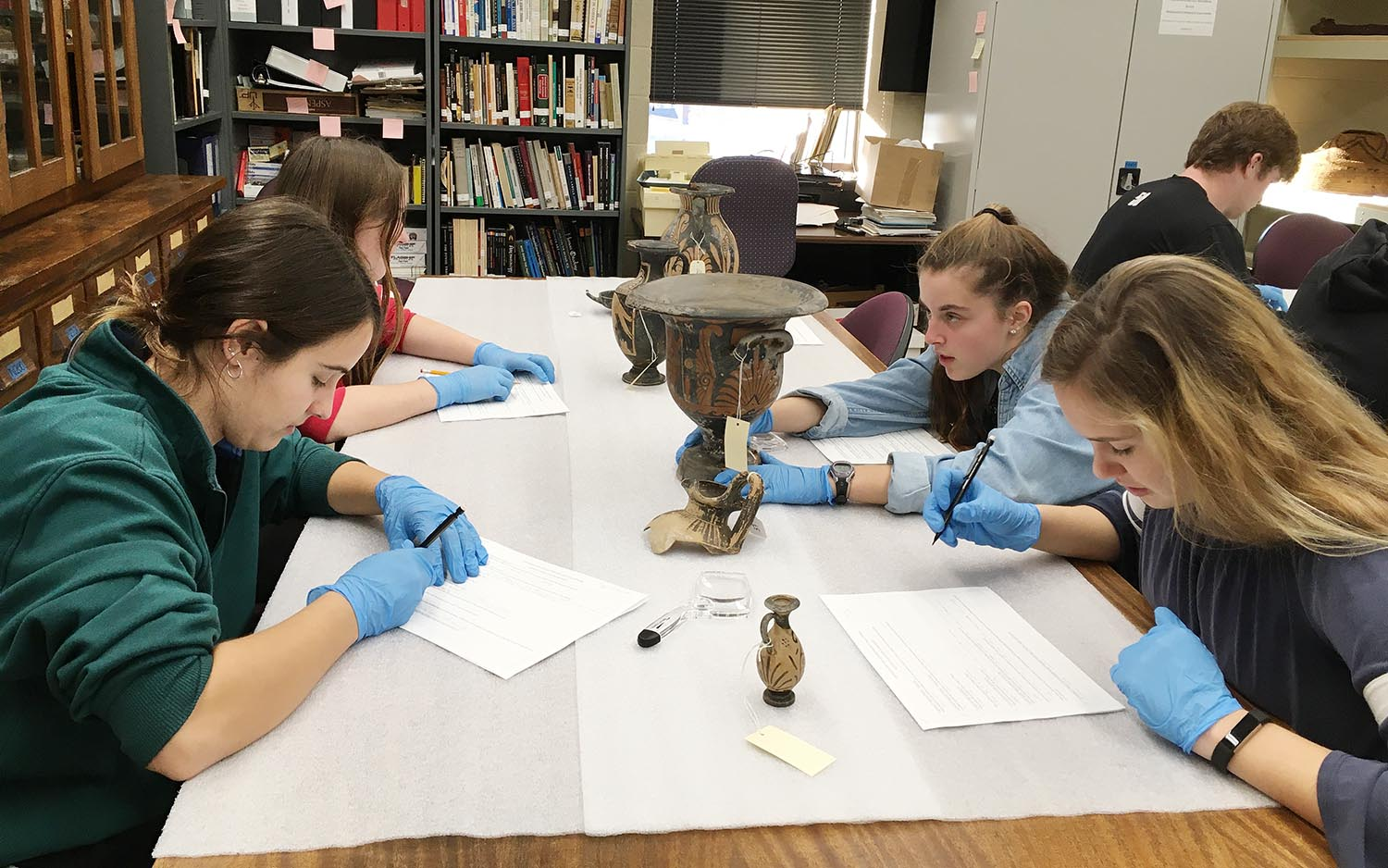The Wesleyan University Archaeology and Anthropology Collections (WUAAC) is located on the third floor of Exley Science Center and contains more than 30,000 archaeological and ethnographic objects from around the world. These objects are used in the hands-on teaching of various subjects, including archaeology, anthropology, history, museum science, classics, and more. Wesleyan faculty and students are encouraged to utilize the collections for teaching and research. Pictured, the class is examining classical Greek pottery