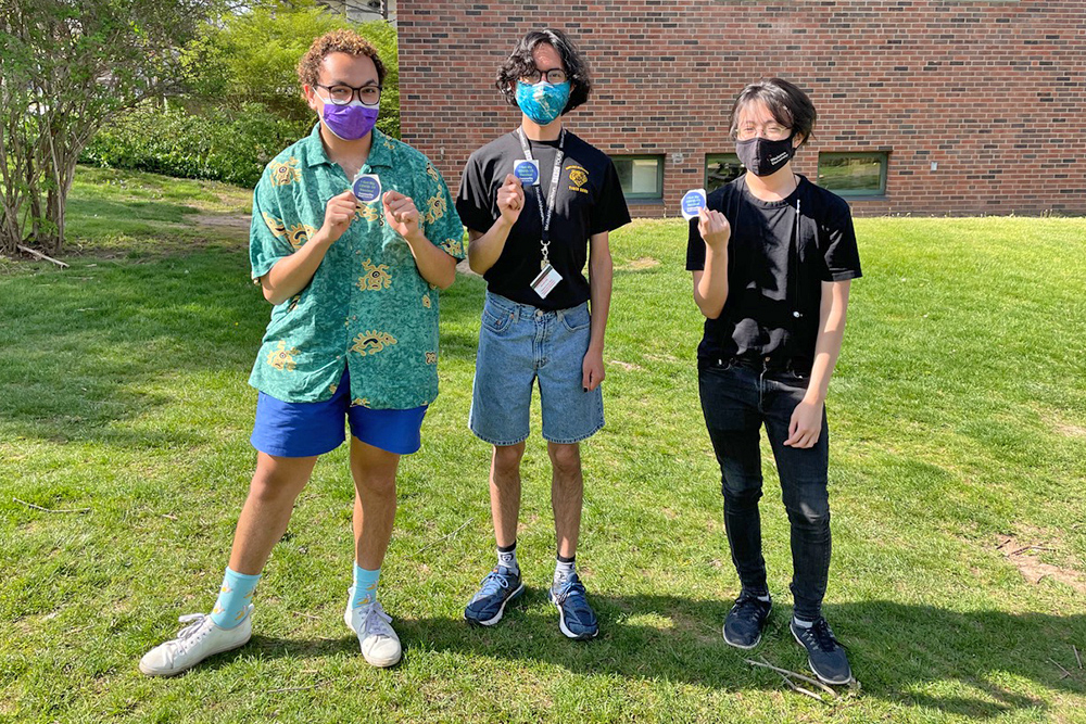 """Vincent Langan '24, Andres Angeles-Paredes '24, and Tuong Nguyen '24 proudly display their """"I'm vaccinated"""" stickers after receiving their first Pfizer COVID-19 vaccination on April 24. """"I feel elated. This is an emotional high,"""" Langan said. """"I am extremely grateful."""" (Photo by Rachel Wachman '24)"""