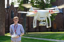 David Schwartz '17, founder and president of the Wesleyan Radio Control/ Drone Club, flies a drone behind South College July 28. He's also on Wesleyan's ski team, rock climbing team and sailing team. (Photo by Olivia Drake)