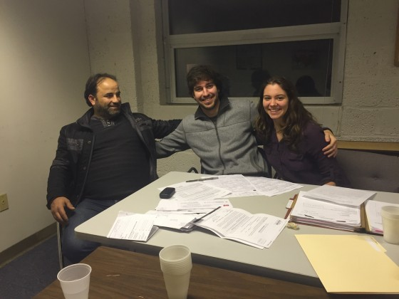 Cole Phillips '16, center, and Sophie Zinser '16, right, volunteer every week at Integrated Refugee and Immigrant Services (IRIS) in New Haven, helping refugees apply for housing and energy subsidy programs. Here, they are pictured with Ramez al-Darwish, a Syrian refugee from Homs.