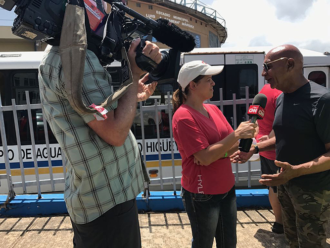 CNN's Maria Santana interviews the mayor of a Puerto Rican city after the Hurricane. In the photo, a CNN cameraman points a video camera on the interview.